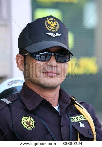 CHIANG MAI, THAILAND. February 25, 2010: Everyday life in Northern Thailand. Closeup portrait of young police officer in the form near the Buddhist temple in Chiang Mai.