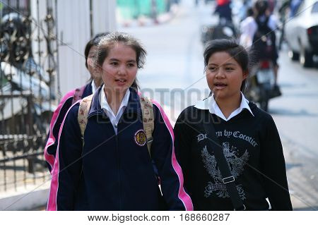 CHIANG MAI, THAILAND. February 25, 2010: Everyday life in Northern Thailand. Schoolgirls walking in the street after school in Chiang Mai.