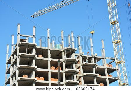 Building cranes on construction site with builders. Crane Construction. Tower Crane Hook and Building Constructors on Construction Site.