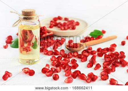 Bottle of pomegranate oil. Natural body care products. Clusters of juicy red seeds scattered white table.