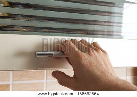 Mans Hand Open The Kitchen Cupboard Doors, Close Up
