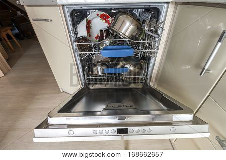 Build-in dishwasher with opened door with clean glass and dishes in modern kitchen selective focus