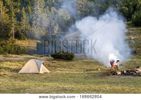 View with a tent camping fire wit smoke and tourist hiker in summer day.