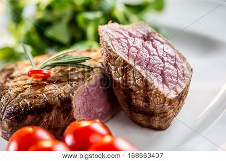 Beef Steak. Juicy beef steak. Gourmet steak with vegetables and glass of rose wine on wooden table.