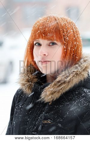 Winter portrait of a cute red-haired girl with blue eyes in a black jacket with fur during a snowstorm red-haired woman stands in the street during a heavy snowfall look at the camera vertical