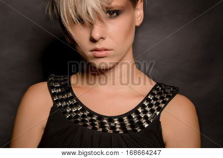 Close-up of a girl with a short haircut. Dark background