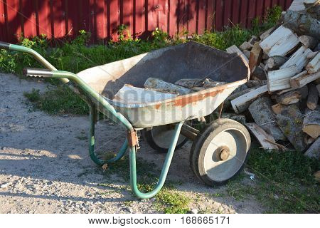 Garden wheelbarrow with firewood. Close up on firewood