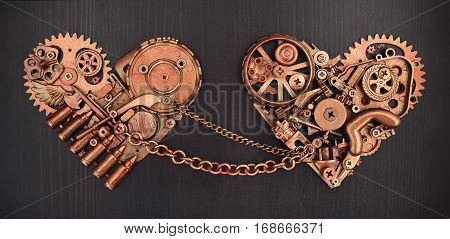 Composition of two chained hearts collected from different mechanical parts on dark wooden background. Valentines Day concept