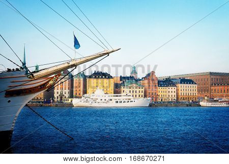 waterfront architecture of old town Gamla Stan in Stockholm with ships embankment, Sweden, retro toned