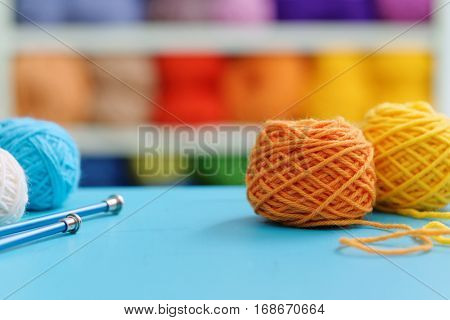 Knitting yarn and needles on blue table against blurred background. Close up of multi colored woolen balls.