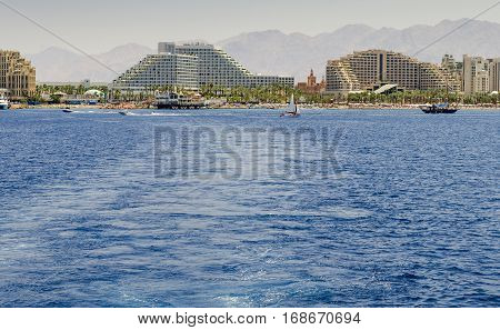 View on the central beach of Eilat - famous resort city in Israel with thousands relaxing tourists from around all the world