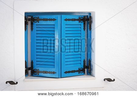 Blue wooden window shutters with vents in white stone wall. Classic resort Greek architecture, white-blue building of house on shore of Cretan sea.
