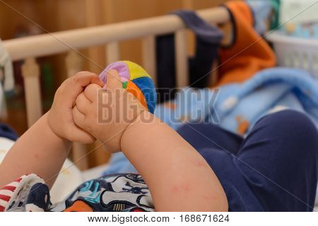 Baby playing in the cot with a small softball - close up