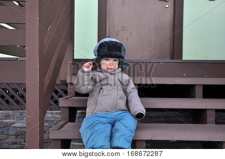 the boy two-year-old in a cap with ear-flaps sits on a porch