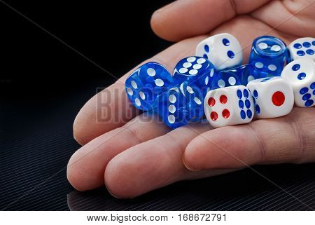 The male hand throwing colored dices on dark background