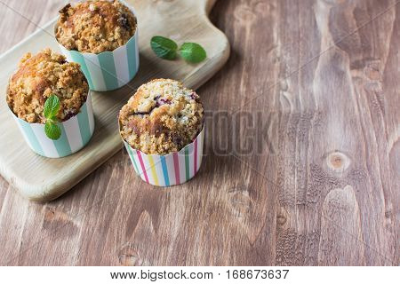 Three muffins in stripy paper cases on the wooden table selective focus