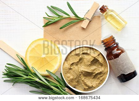 Preparing homemade skincare mask with natural ingredients: bentonite clay, rosemary, lemon slice, essential oil, note for recipe.