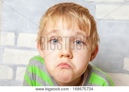 Portrait of adorable sad funny child on wall background