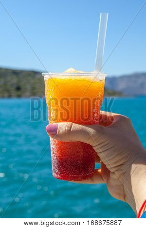 Frozen layered fruit drink in a woman hand