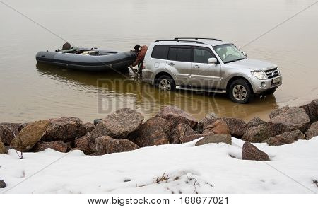 Saint-Petersburg, Russia - March 05 2016: Man is released from the car Mitsubishi Pajero had brought the boat on the pond