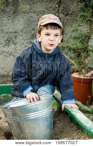 The boy in a sandbox with a shiny bucket jacket jeans and cap crouching playfully arguing against the background of gray walls and small trees.