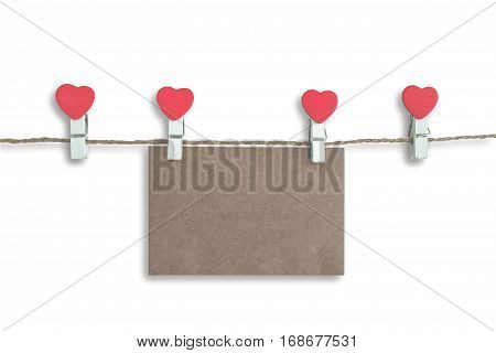 wooden clothespin with heart shape design and brown paper sheet for valentine concept isolated on white background