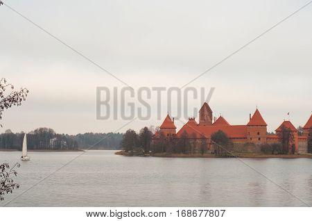 Yacht sailing at lake near Trakai Peninsula Castle Museum on the island. Village of Karaites, Lithuania, Europe. Lithuanian landmark in late autumn