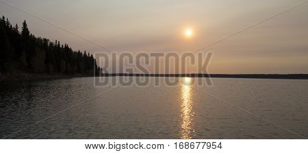 Smoke from a fire in nearby Albert adds color over Dore Lake Saskatchewan at dawn