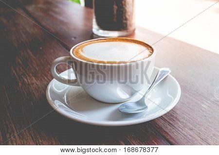 hot coffee mocha with foam milk in vintage cafe(vintage effect)