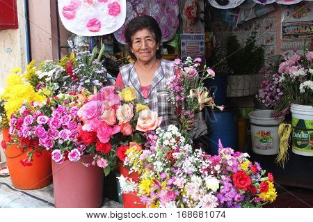 Laredo Peru - January 28 2017: Woman sells fresh flowers from flower stall at market in Laredo Peru on January 28 2017