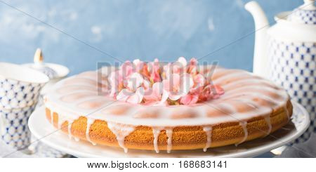 Bundt ring cake with sugar frosting decorated with pink flowers. Spring summer elegant breakfast set. Easter mother day festive treat. Selective focus banner