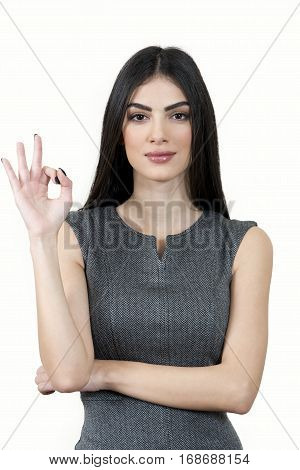 Young business woman looking at the camera and doing the ok sign.