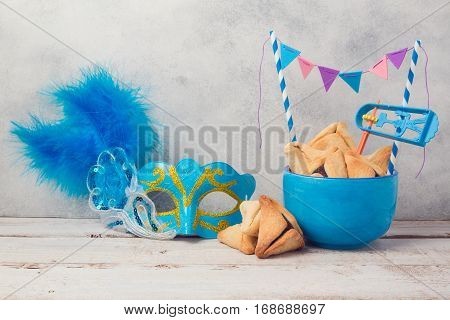 Purim celebration concept with hamantaschen cookies and carnival mask on wooden table