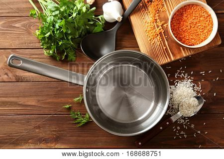 Stainless saucepan, parsley and lentil on wooden background