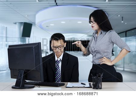 Portrait of angry boss pointing to her subordinate while standing in the office