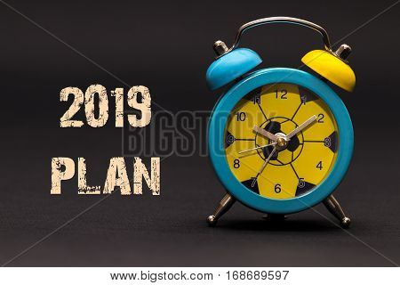 2019 Plan Written With Alarm Clock On Black Paper Background