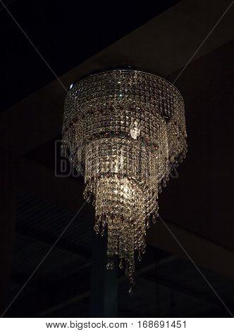 Modern glass chandelier on a black background. Interior