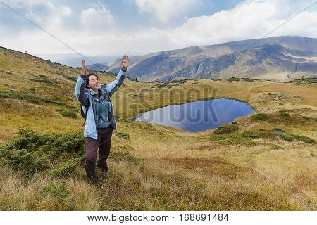 Girl tourist in the mountains emotionally gesticulates. People