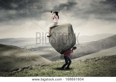 Businessman lifting a big stone on the hill while his partner sitting on the stone and looking through binoculars