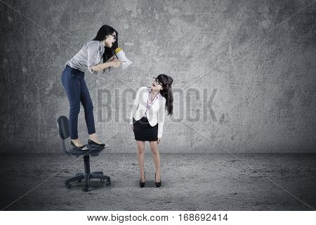 Picture of young businesswoman yelling to her employee by using a megaphone while standing on the chair