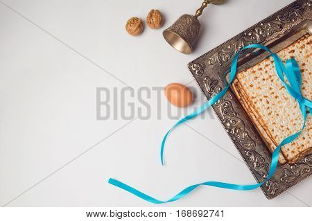 Jewish holiday Passover concept with matzah egg and wine glass on white background. View from above. Flat lay