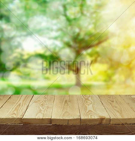 Empty wooden deck table with foliage bokeh background for product display montage. Spring or summer concept