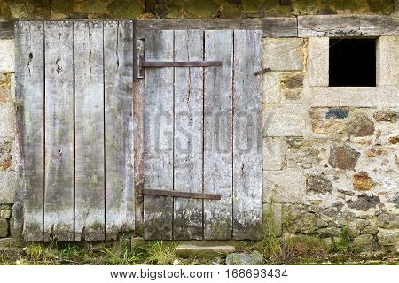 Weathered old stone barn with a closed wooden door in Brittany France