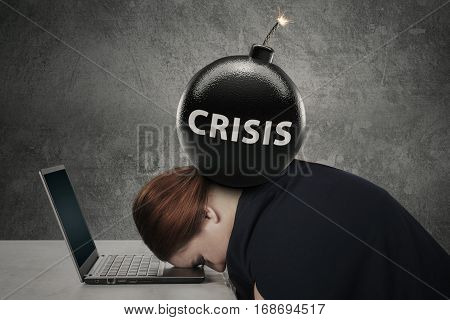 Young entrepreneur sleeping on the laptop with text of crisis on the bomb over her head
