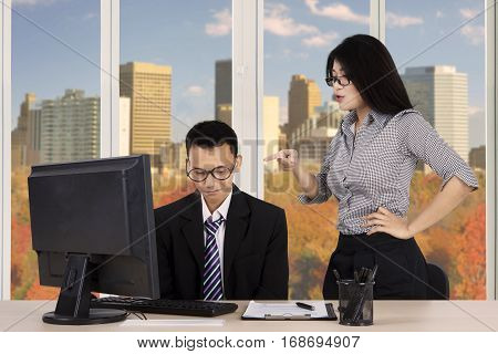 Portrait of female boss pointing to her employee as angry expression with autumn background on the window