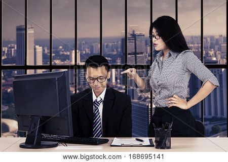 Portrait of female entrepreneur feels angry to her subordinate while stands in the office