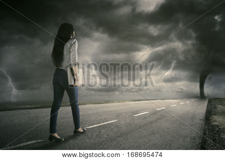 Image of a female entrepreneur walking on the street while holding a laptop with storm on the sky