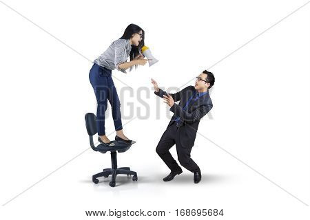 Picture of female entrepreneur shouting to her subordinate with megaphone while standing on the chair isolated on white background