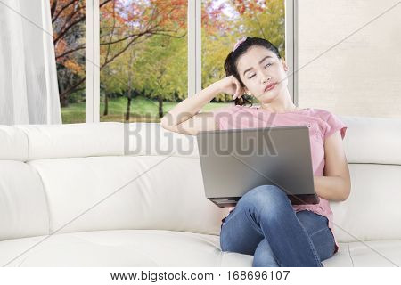 Portrait of a female model sitting on the couch and looks sleepy with a laptop computer shot with autumn background on the window