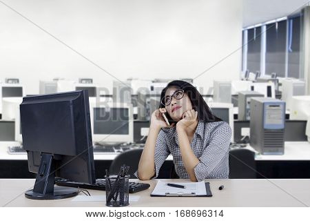 Portrait of female worker listening her mobile phone while daydreaming in the office